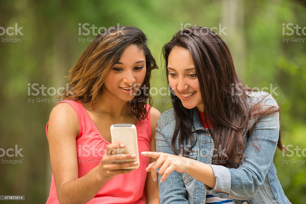 Young adult girl friends view video on smart phone. Outdoors. stock photo