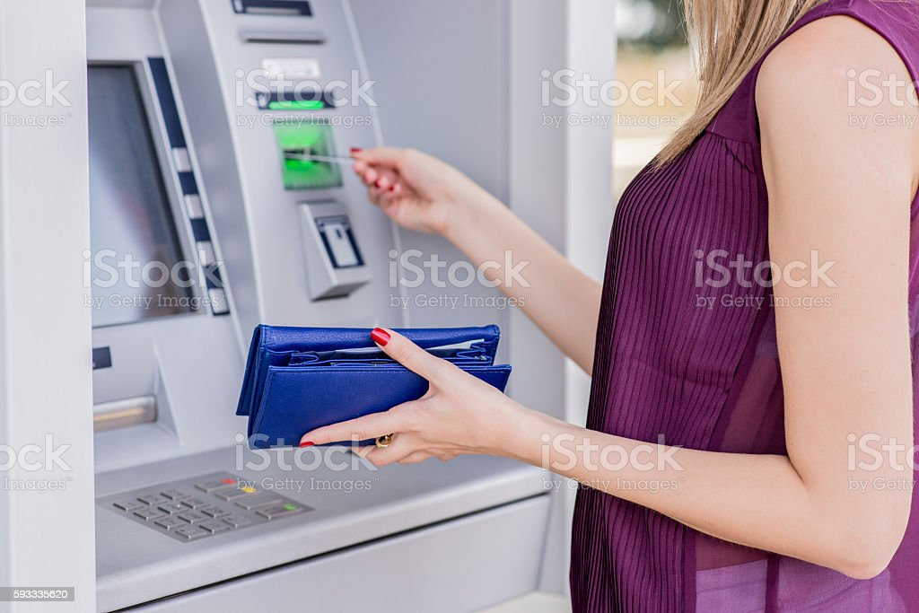 Young adult girl inserting credit card on ATM stock photo