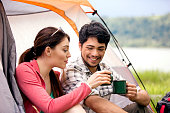 Young adult heterosexual couple toasting to a camping weekend