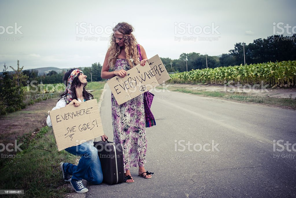 Young adult hippie couple hitchhiking with placards in hand stock photo