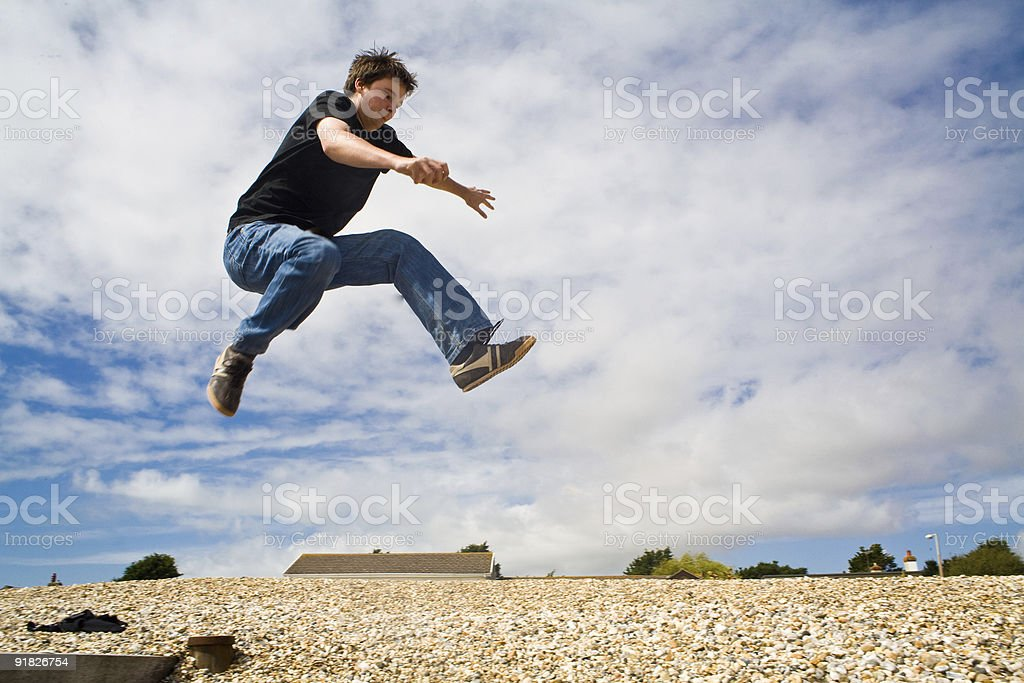 Young adult jumping over rocky beach stock photo