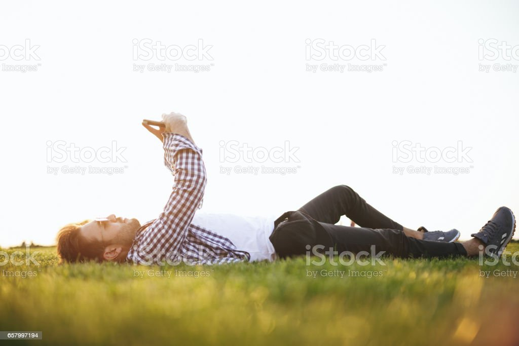 Young adult lying down on grass using smartphone stock photo