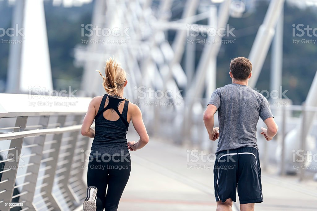 Young adult male and female running across a bridge stock photo