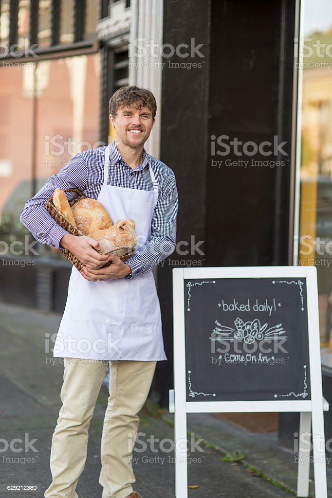 Young adult male baker standing outside his small downtown business stock photo