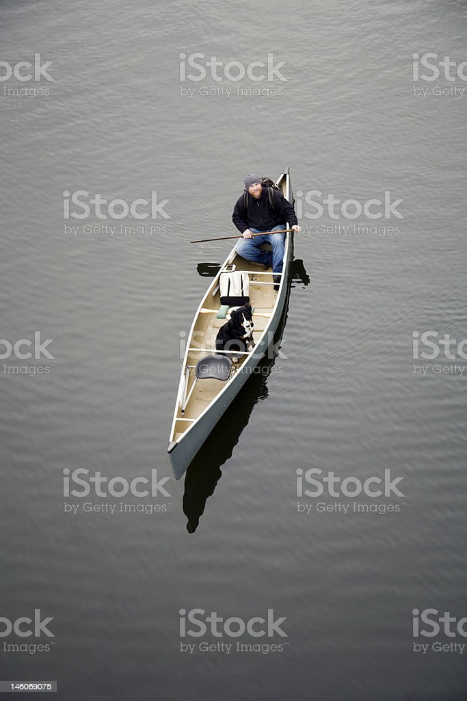 Young Adult  Male Canoeing With His Dog On Lake royalty-free stock photo