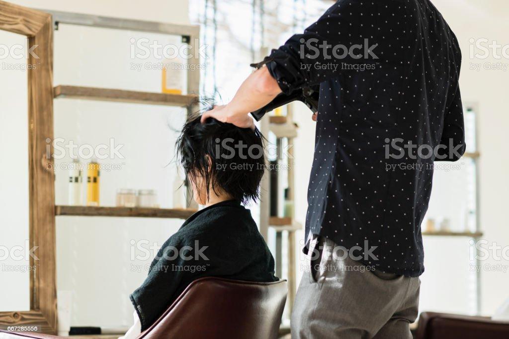 Mid adult woman at a hair salon.Professional hairdresser at hair salon