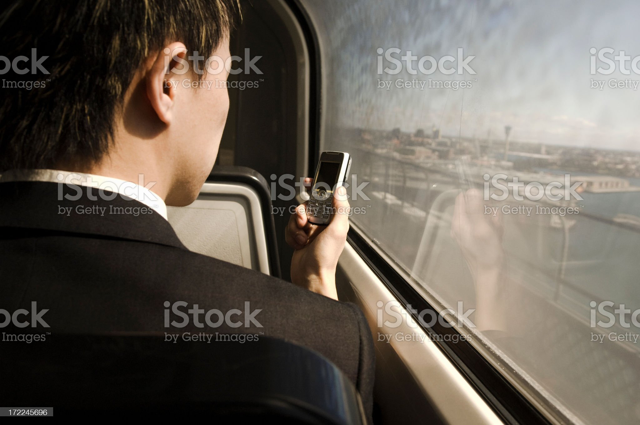 Young adult male on train with cell phone royalty-free stock photo