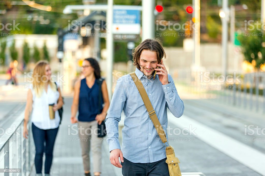 Young adult male professional walking to public transit station stock photo