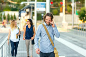 Young adult male professional walking to public transit station