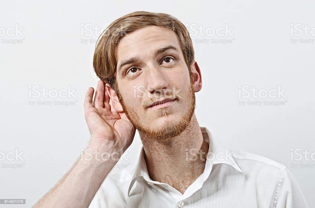 Young Adult Male with His Hand Near His Ear stock photo