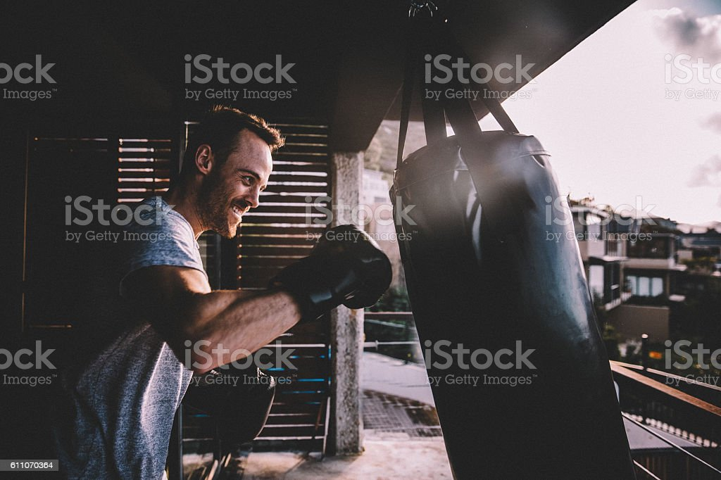 Young adult man doing boxing workout at home stock photo