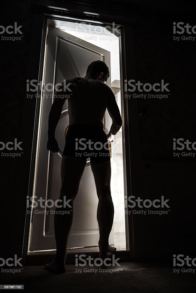 Young adult man enters opening door from dark stock photo