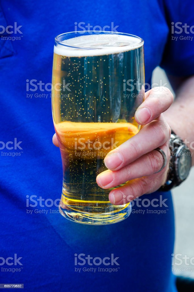 Young adult man holds paint of lager beer stock photo
