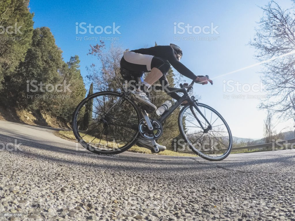 Low angle view of a young adult man riding a racing bicycle on a...