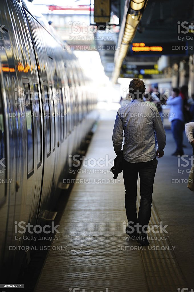 Young adult man walking along waiting train on station platform royalty-free stock photo