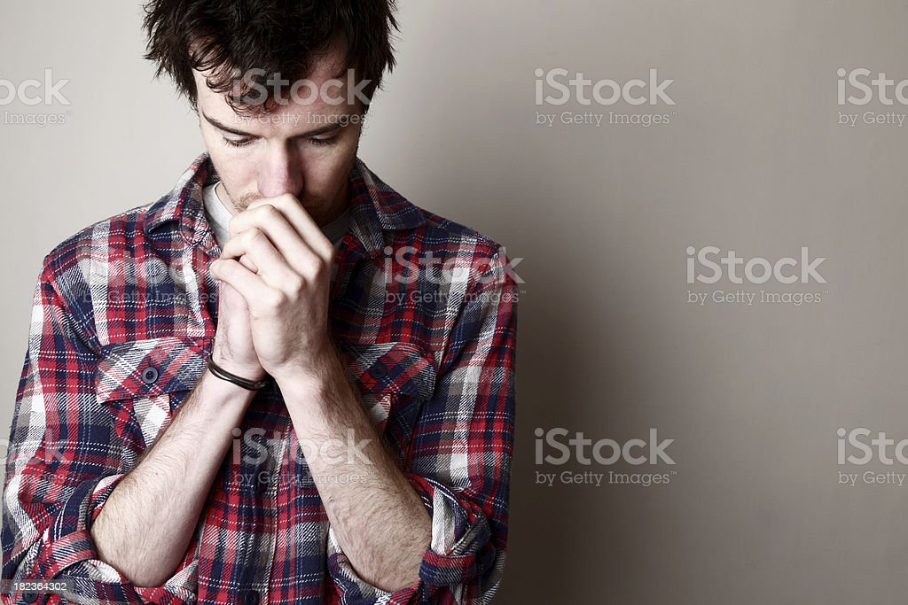 Young adult man, worried, against wall  stock photo