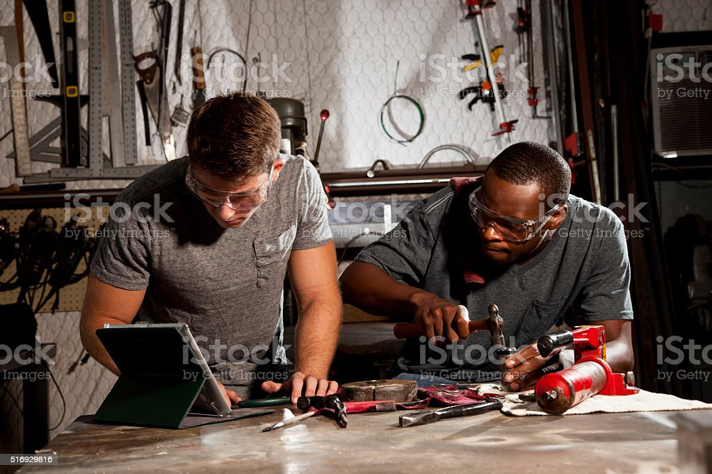 Young adult mechanics in small business repair, workshop.  Digital tablet. stock photo