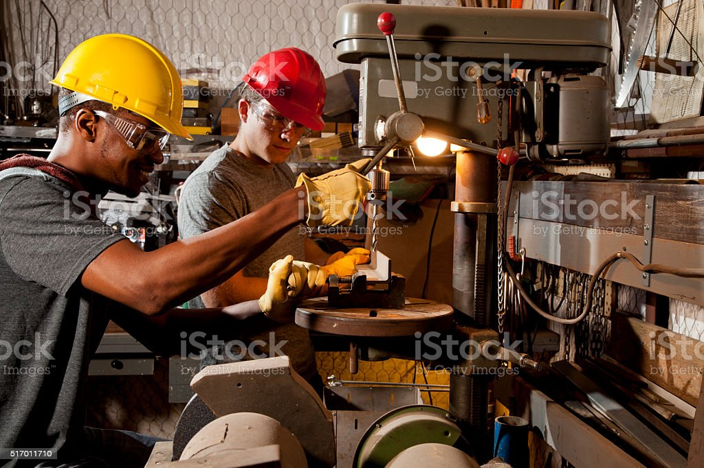 Young adult mechanics in small business repair, workshop. Drill press. stock photo