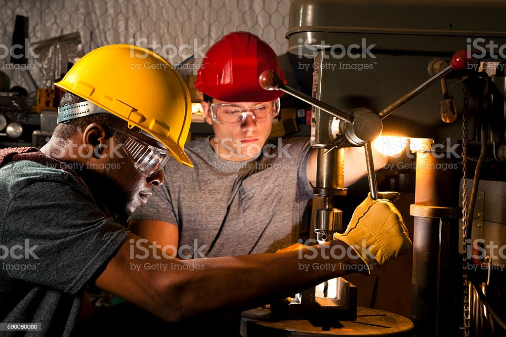Young adult mechanics in small business repair, workshop using press. stock photo