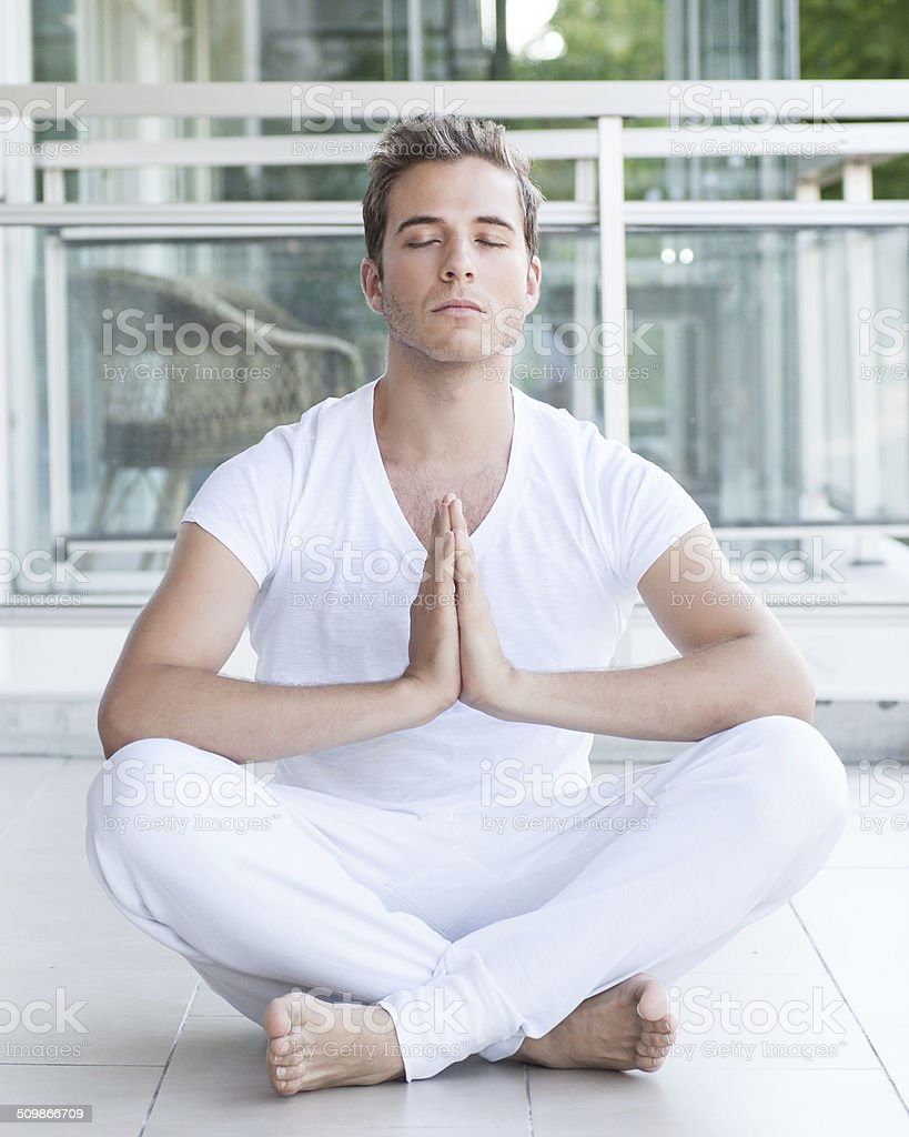Young adult meditating with hands together stock photo