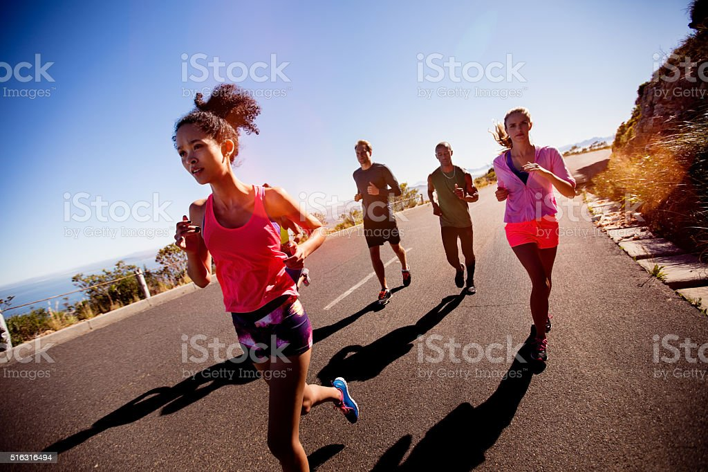 Young adult multi-ethnic group of athletes running outdoors stock photo