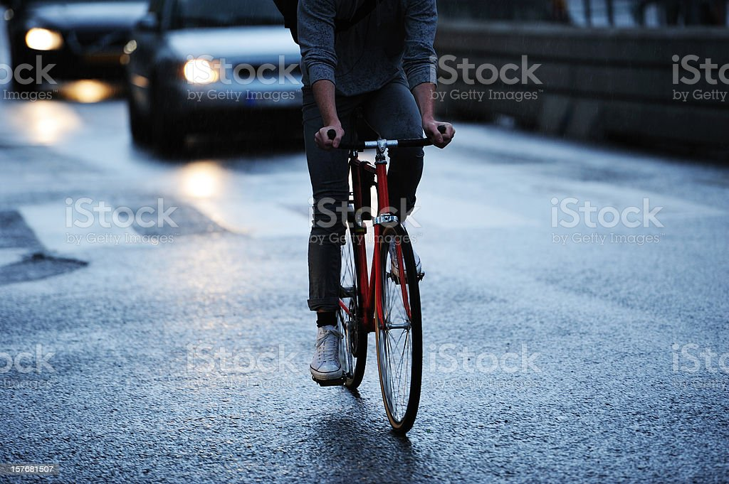 Young adult on bike in the city, rainy evening traffic royalty-free stock photo