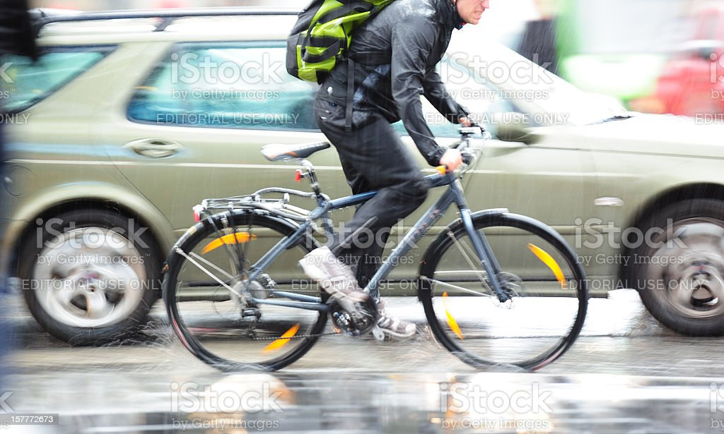 Young adult on bike in the city, rainy evening traffic stock photo