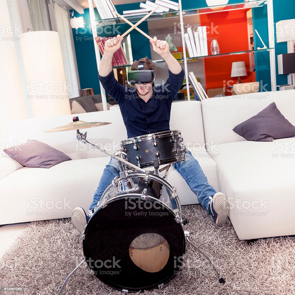 young adult playing drums at home using viewer stock photo