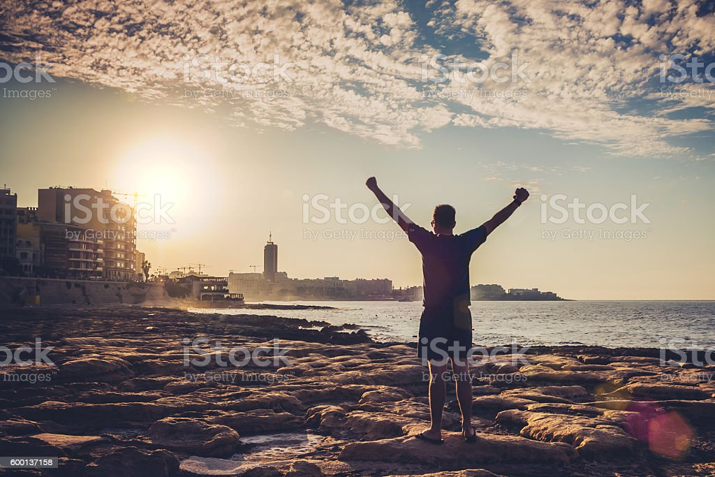 Young adult raising arms to the sea at sunset stock photo