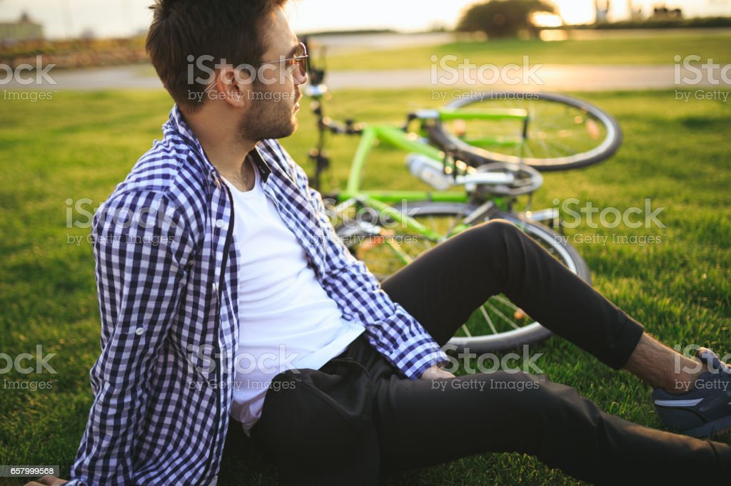 Young adult sitting on grass stock photo