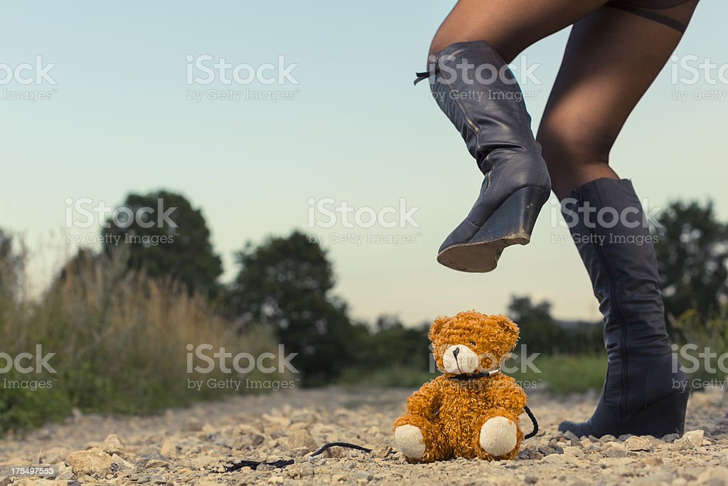 Young adult stomping on teddy bear stock photo