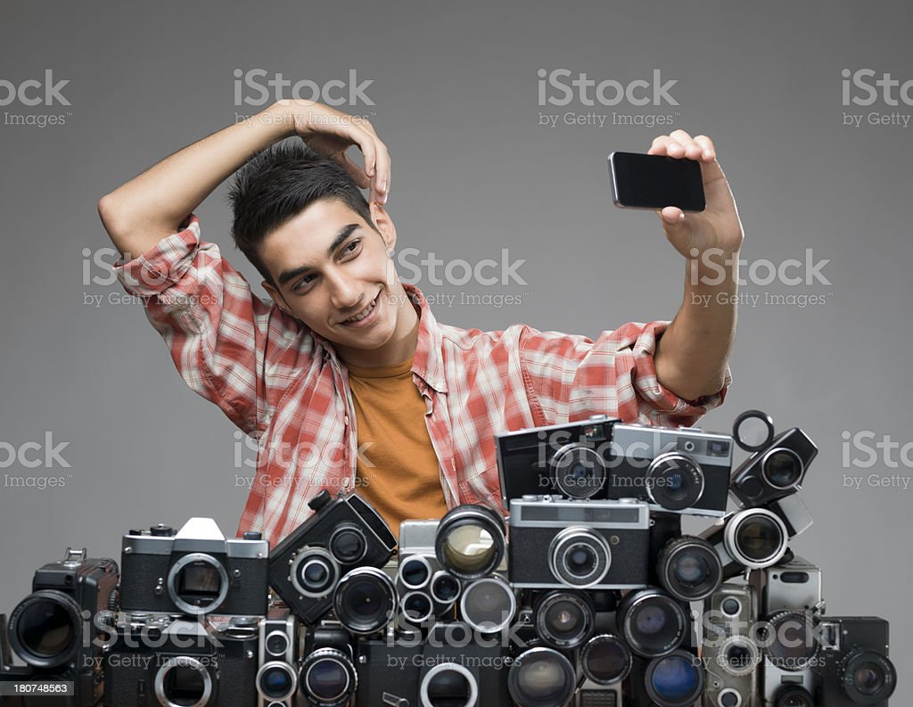 Young adult taking his self portrait via smartphone stock photo
