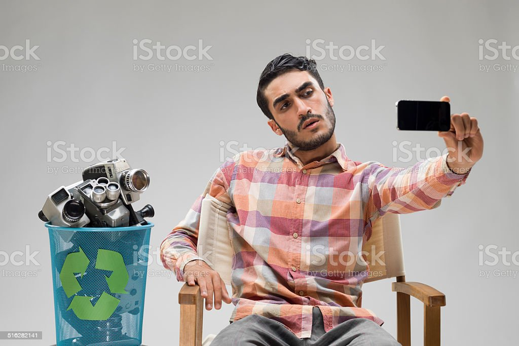 Young adult taking his selfie portrait via smartphone stock photo
