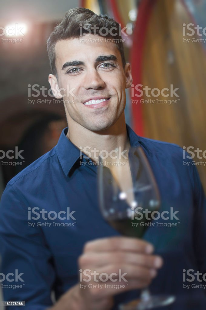Young adult tasting wine in a wine cellar stock photo