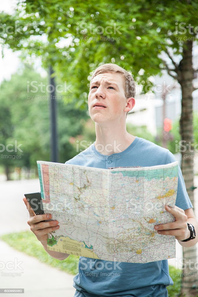 Young adult tourist in urban downtown city with map. stock photo