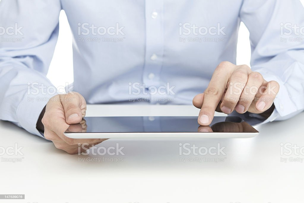 Young adult wearing light blue shirt working on a tablet royalty-free stock photo