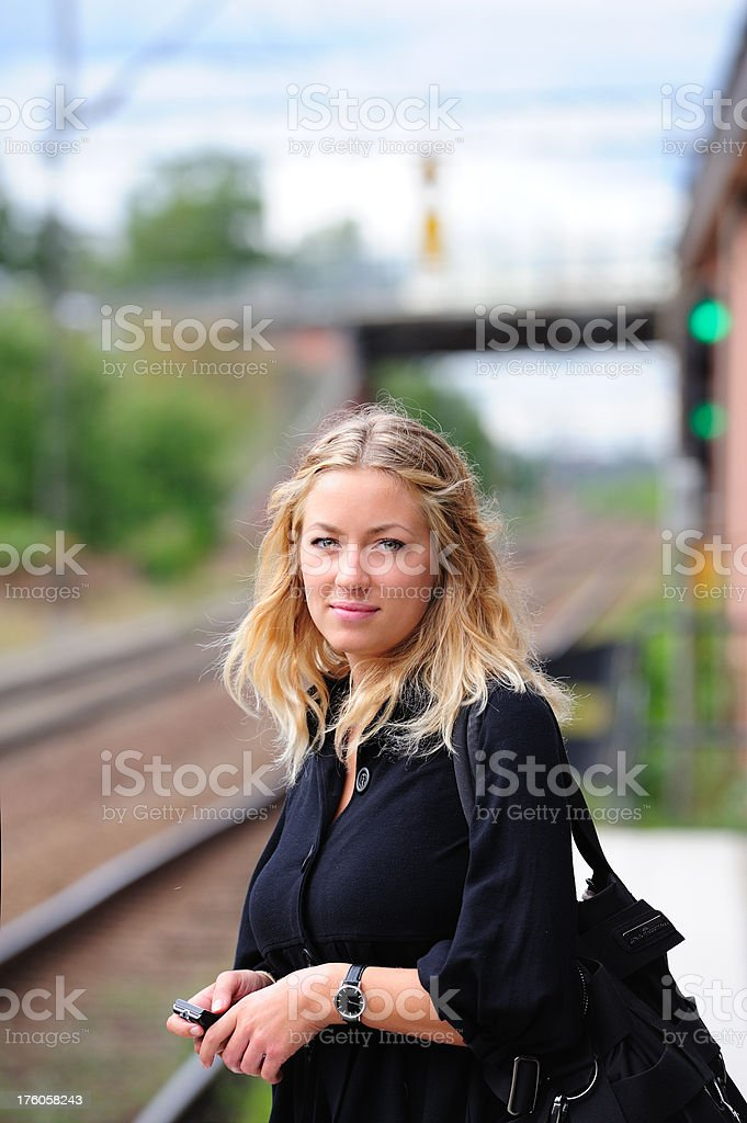 Young adult with mobile phone waiting for train royalty-free stock photo