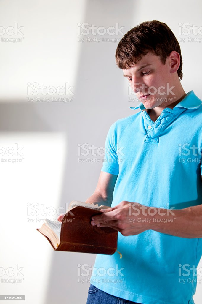 Young adult with open Bible. Cross shadow in background. royalty-free stock photo