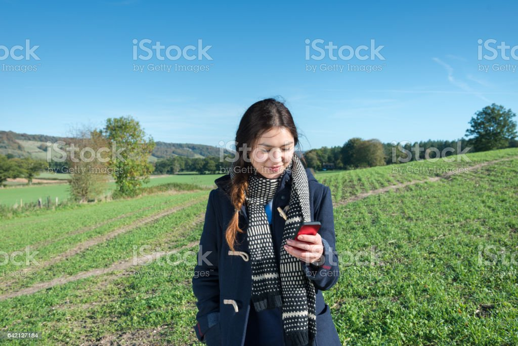 Young adult woman and mobile phone, fields, fall clothes stock photo