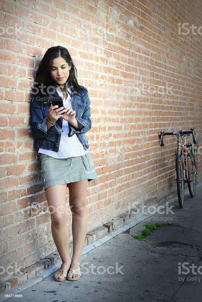 Young adult woman and phone, bike in background stock photo