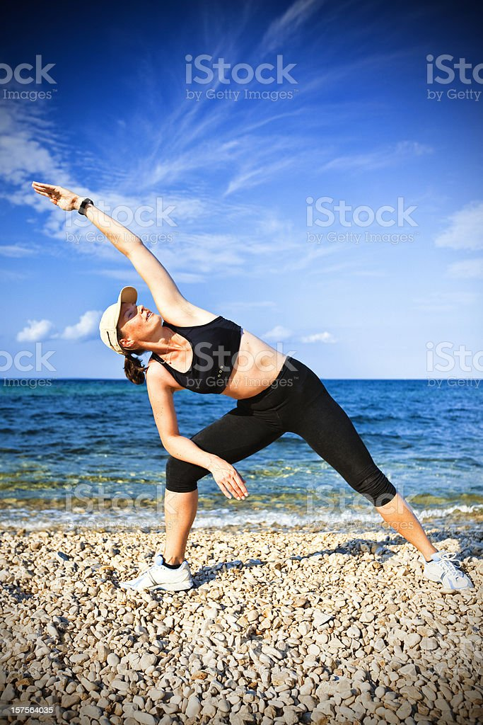 Young adult woman doing yoga exercise on beach in morning royalty-free stock photo