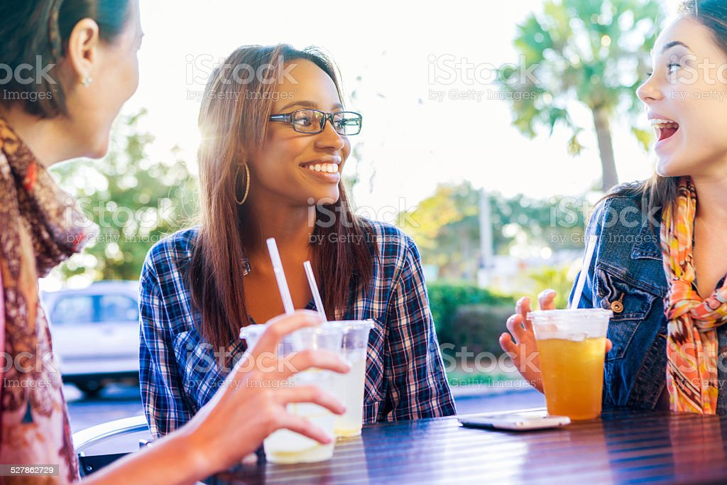 Young adult women enjoying drinks together on patio stock photo