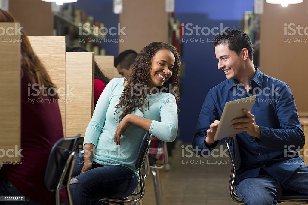 Young adults commenting in library stock photo
