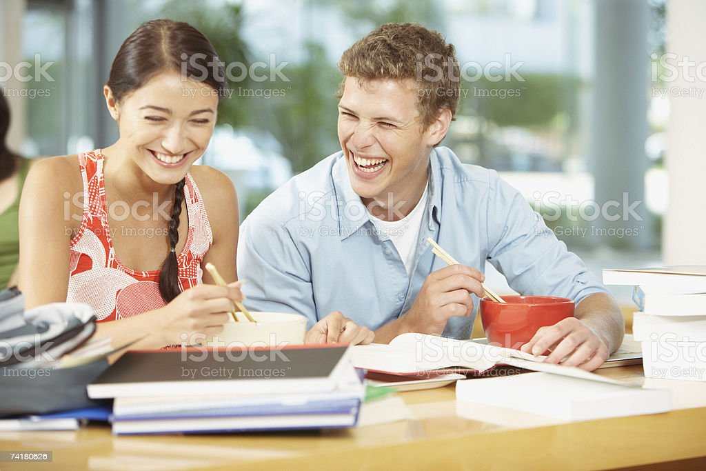 Young adults eating bowls of noodles with chopsticks in high school cafeteria stock photo