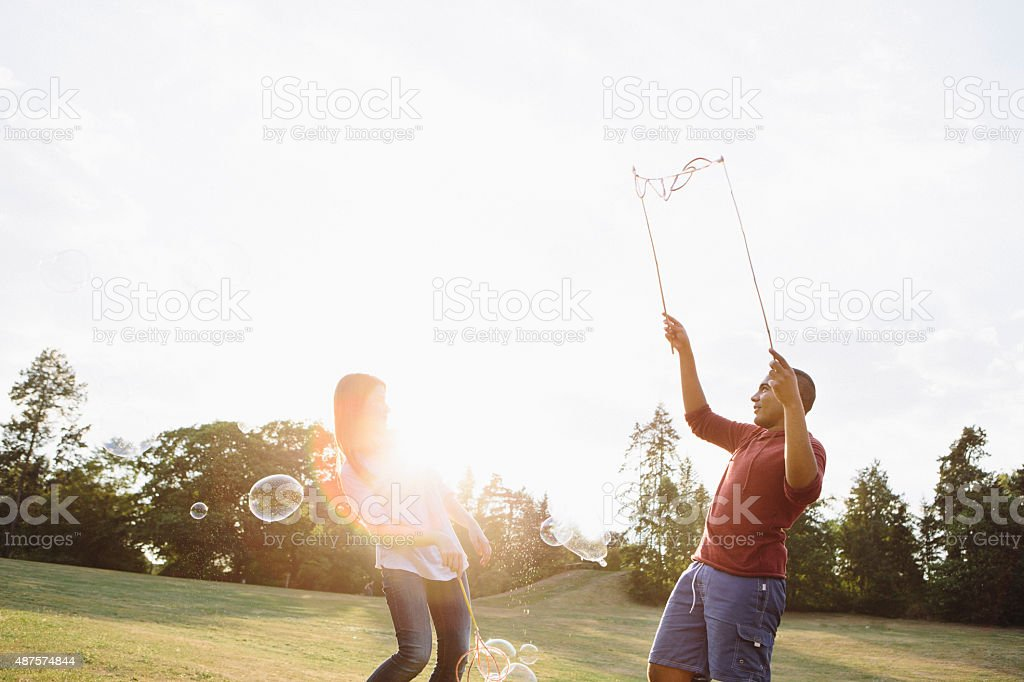 young adults having fun with soap bubbles, back lit stock photo