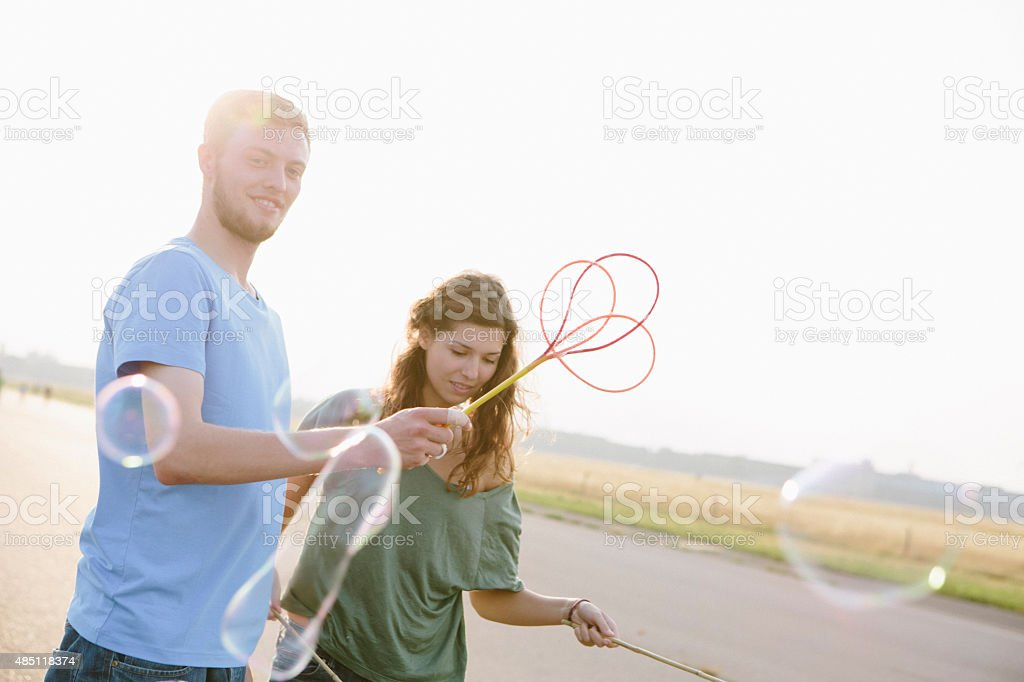 young adults having fun with soap bubbles stock photo