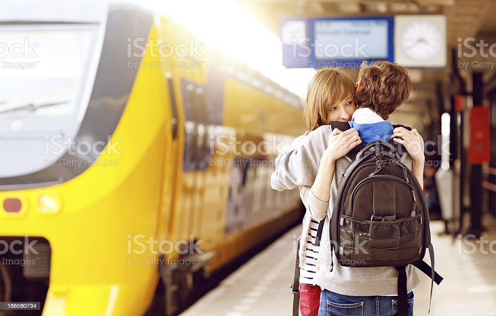 young adults hugging at the railway station stock photo