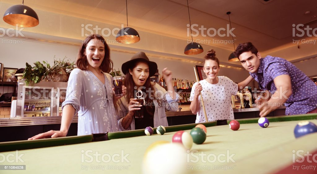 Young adults in bar, playing pool stock photo