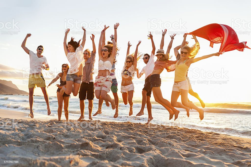 Young adults jumping in unison on the beach stock photo