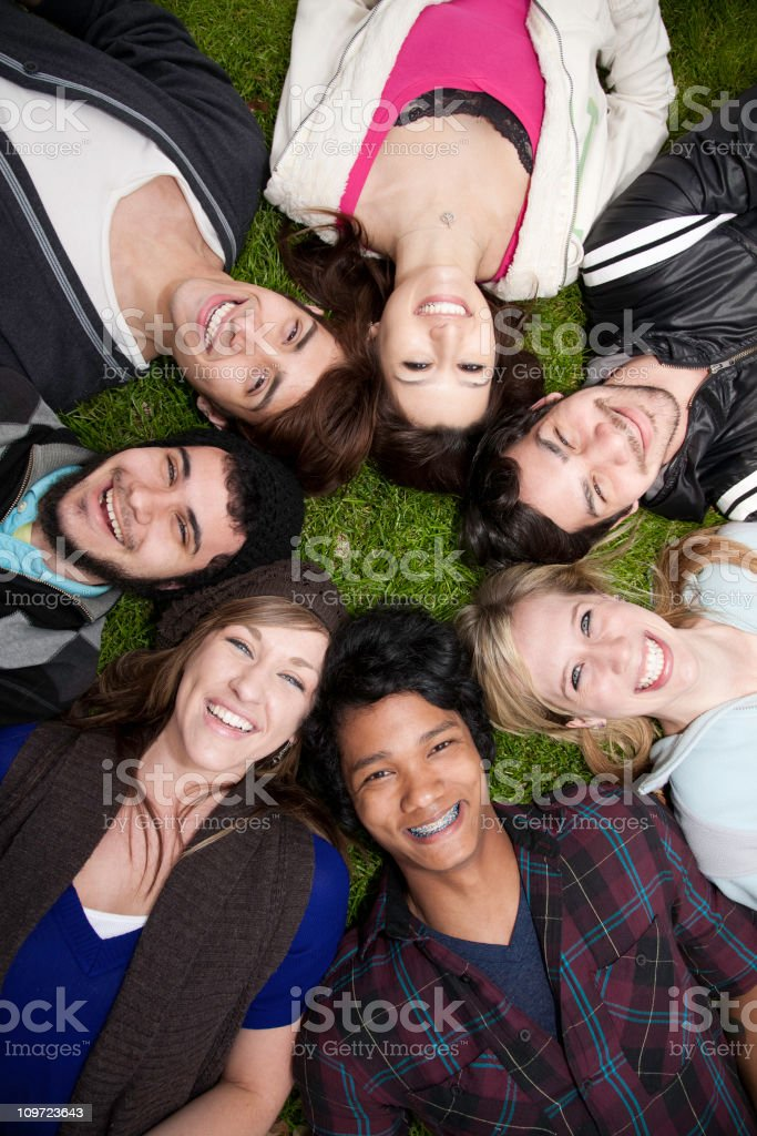 Young Adults Lying in a Circle on the Grass royalty-free stock photo